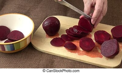 Woman hands slicing beetroot on wooden cutting board. Home...