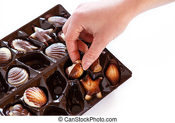 Woman hands taking chocolate candy in box