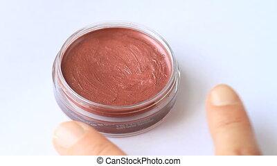 gloss - woman hands taking red lipstick gloss