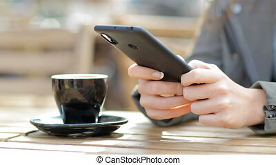 Woman hands texting on smart phone in a cafe terrace