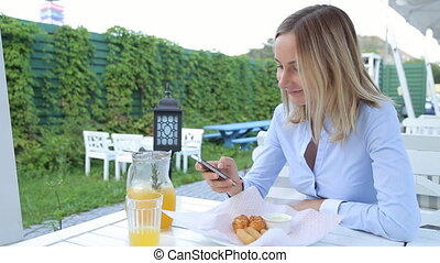 Woman hands texting on smartphone during breakfast in cafe