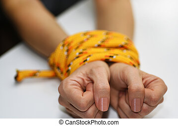 Woman hands tied with rope.