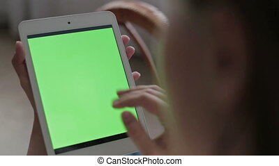 Woman hands touching and scrolling tablet.green screen display