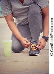 Woman hands tying shoelaces and smartwatch with green vegetable smoothie.