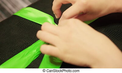 Woman hands untie green ribbon on black gift box. Lockdown...