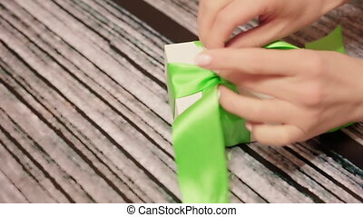 Woman hands untie green ribbon on gift box. Lockdown shot of...