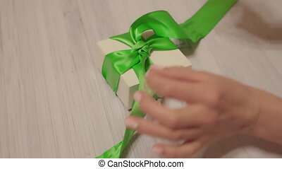 Woman hands untie green ribbon on white gift box. Lockdown...