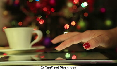 Woman hands using digital tablet with colorful light bokeh...