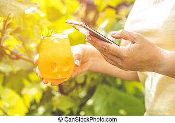 Woman hands using mobile phone and holding refreshing orange...