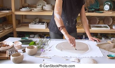 Woman hands using rolling pin, ceramic dish