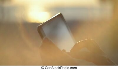 Woman Hands Using Tablet On The Beach