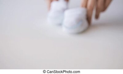 woman hands with baby bootees at home 11 - motherhood,...