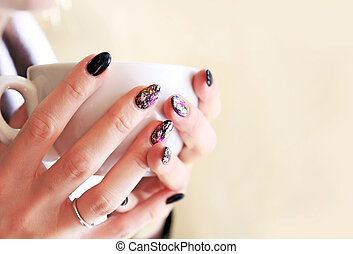 woman hands with beautiful manicure holding a cup of coffee