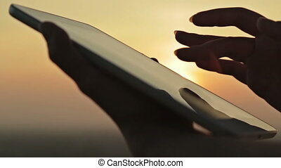 Woman hands with digital tablet at sunset