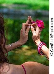 woman hands with flower in yoga mudra gesture outdoor in...