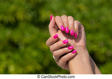 Woman hands with manicured pink nails closeup. Skin and nail...
