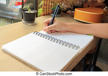 Woman hands with pen writing on notebook