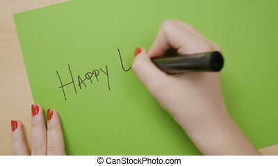Woman hands with red manicure writing happy easter in...