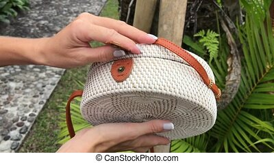 Woman hands with stylich eco friendly rattan bag on a...
