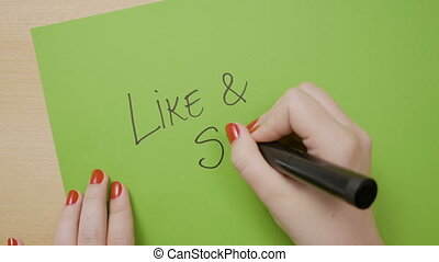 Woman hands writing like and share in capital letters and...