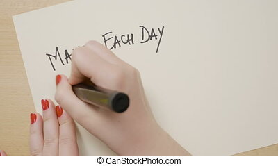 Woman hands writing make each day your masterpiece...