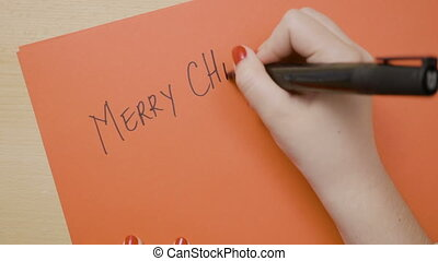 Woman hands writing merry christmas in capital letters on a...
