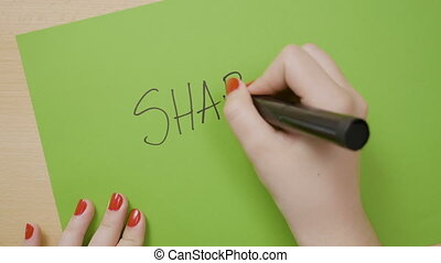 Woman hands writing share in capital letters and underlining...