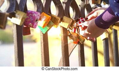 Woman hang a padlock of love closeup