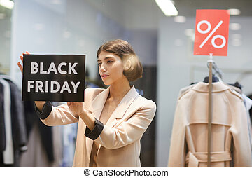 Woman Hanging Black Friday Sign in Store