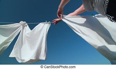 Woman hanging freshly laundered white linens on clothesline against blue sky