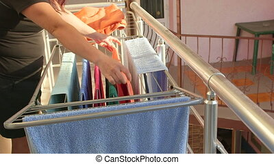 Woman hanging laundry on balcony extended clothes drying...
