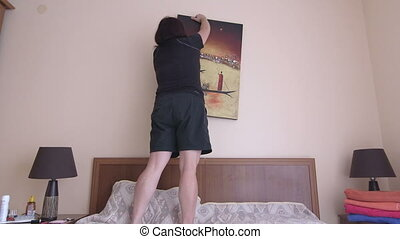 Woman hanging picture frame on the wall at home