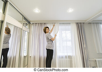 Woman hanging up his curtains at  window