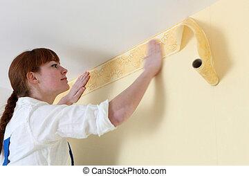Woman hanging wallpaper motif
