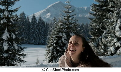 Woman happily throws hands snow in the woods on against mountains.
