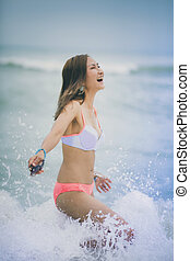 woman happiness emotion with splashing sea beach wave