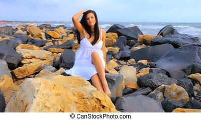 Woman happy on rocks on the ocean