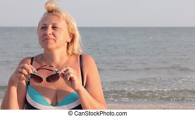 Woman happy on vacation taking off glasses and sunbathing on the beach.