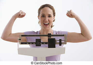 A young woman flexes her arms while standing on a scale and smiling at the camera. Horizontal shot. Isolated on white.