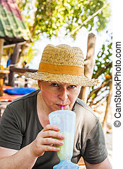 woman has a fruit drink in the tropical restaurant - woman...