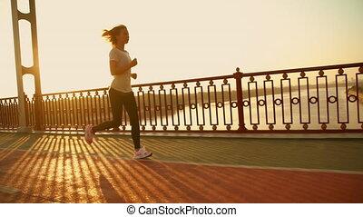 woman has an outdoor workout - female runner against sunset...