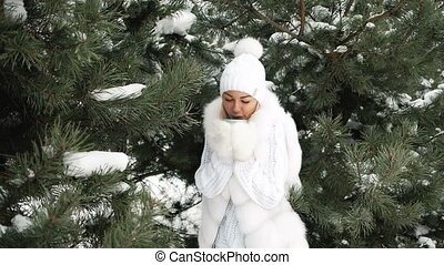 woman has hot tea to get warmed on cold wind, winter landscape.