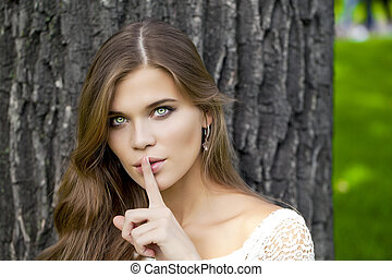 Woman has put forefinger to lips as sign of silence - Young...