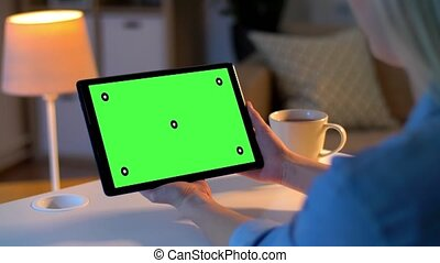 woman has video call on tablet with green screen