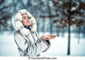 Woman have fun on the snow in winter forest