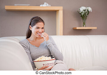 Woman having a bowl of popcorn while watching a movie