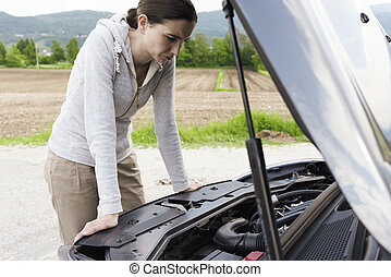 Young helpless woman having a car breakdown in a coutryside road, she is leaning on the car with hood up
