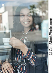 woman having a coffee through the glass