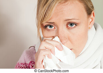 Woman sneezing, having a flu and looking feverish