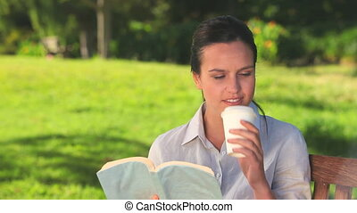 Woman having a drink and reading